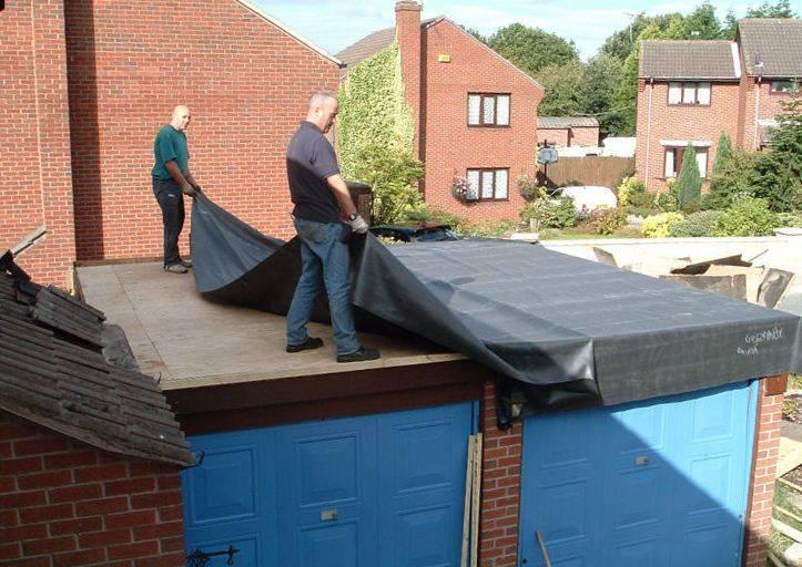 Тентом мужчины покрывают крышу